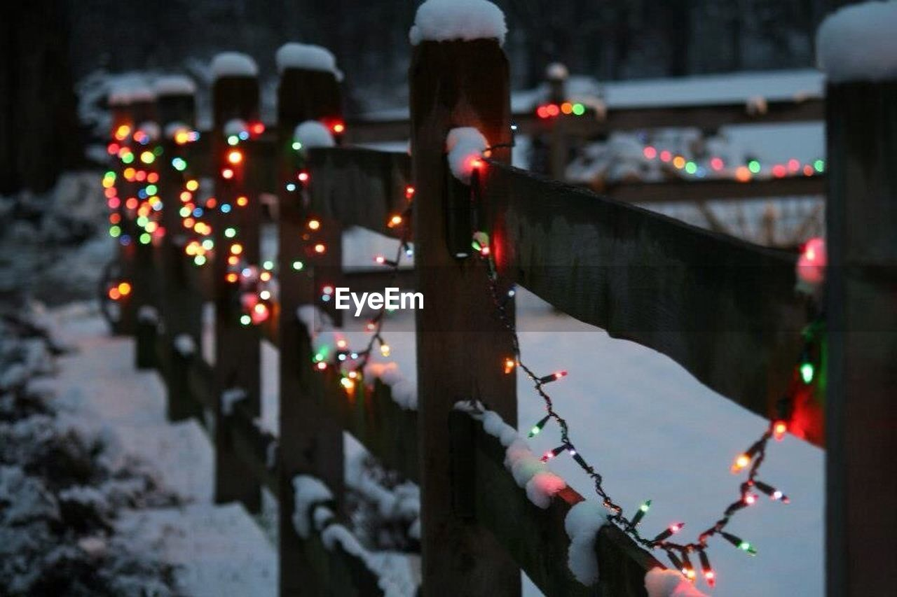 Close-up of fairy lights on fence