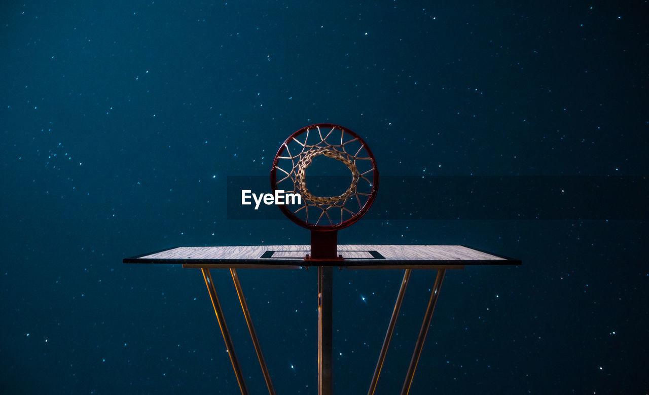 Directly below view of basketball hoop against constellation in sky