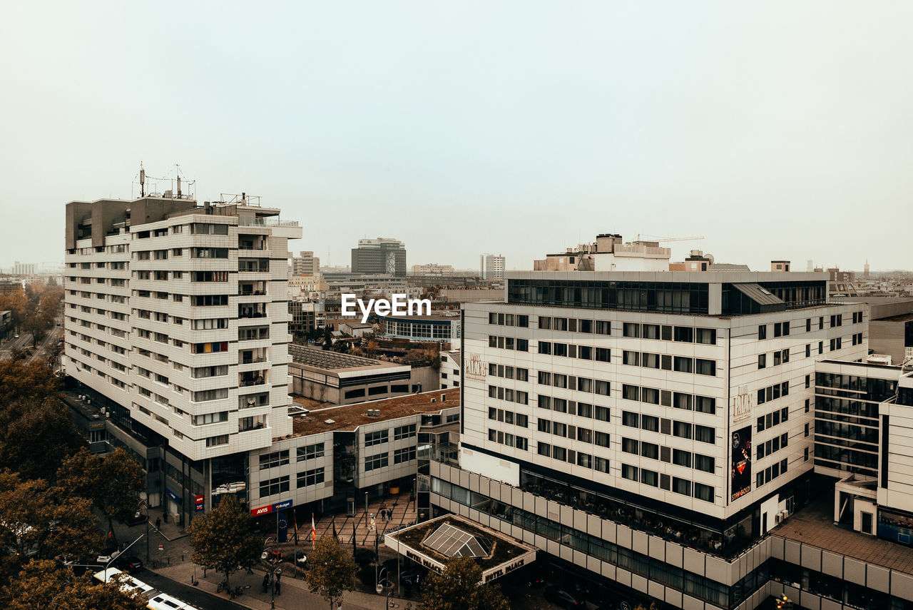 building exterior, built structure, architecture, city, building, sky, nature, residential district, no people, day, high angle view, outdoors, copy space, cityscape, clear sky, development, city life, land vehicle, tall - high, apartment