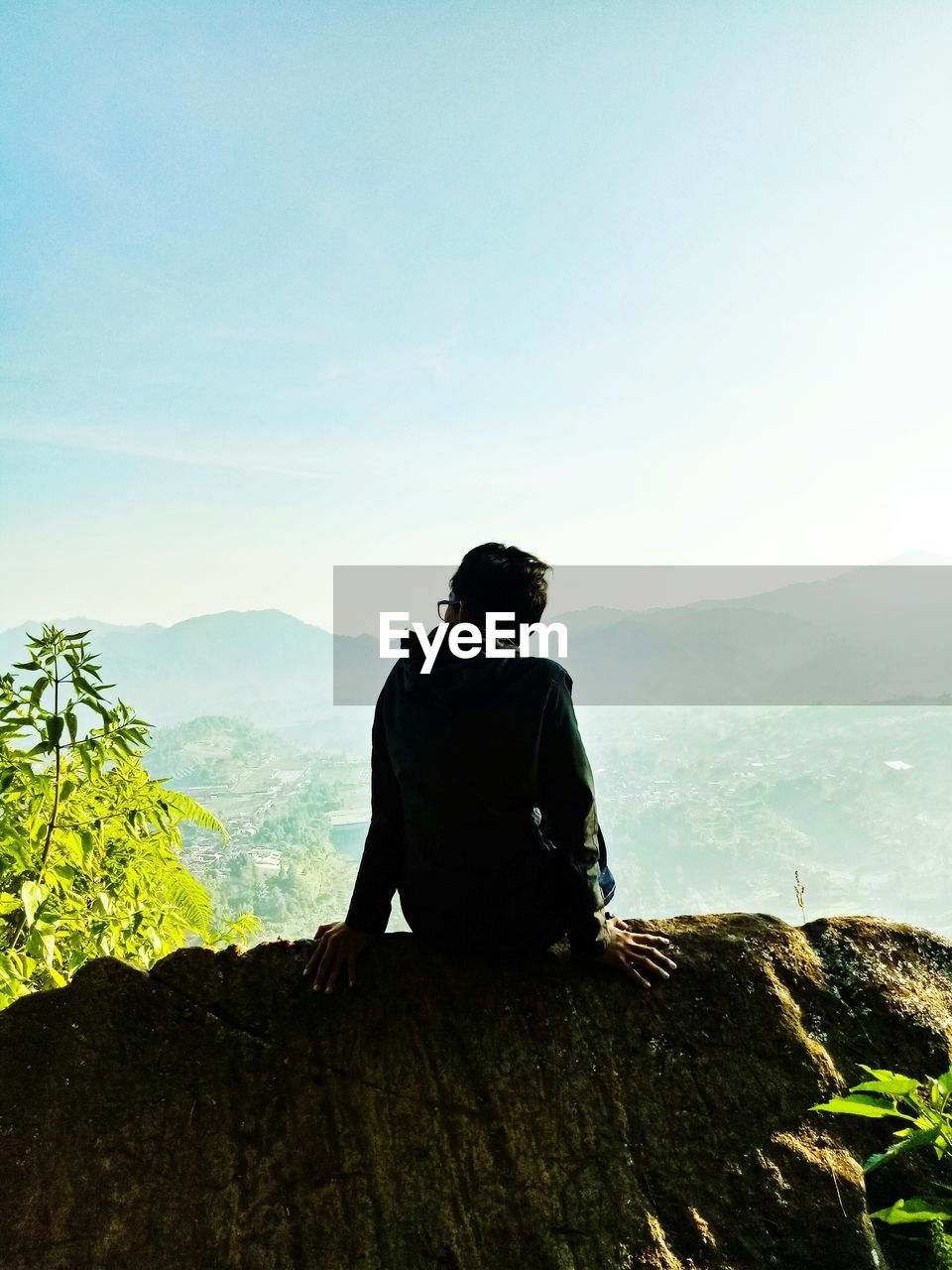 mountain, nature, real people, one person, mountain range, leisure activity, beauty in nature, lifestyles, clear sky, scenics, sky, day, tranquil scene, outdoors, casual clothing, landscape, men, tranquility, standing, sitting, full length, young adult, people