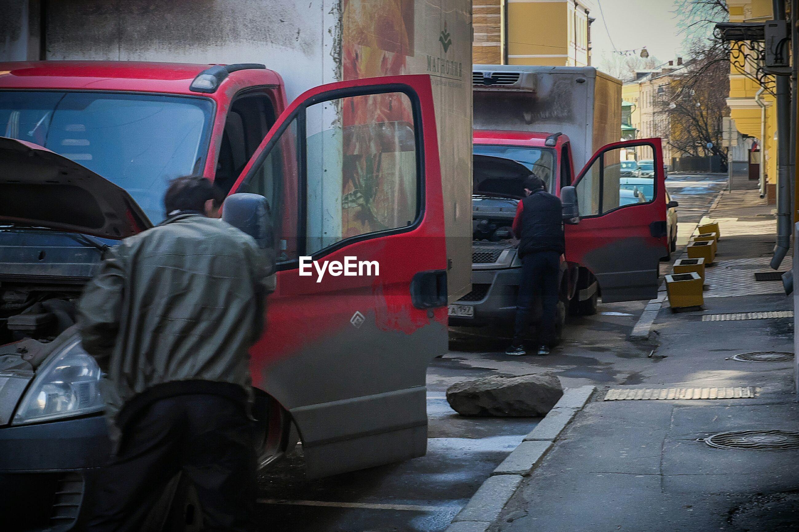 Rear view of men repairing truck on city street