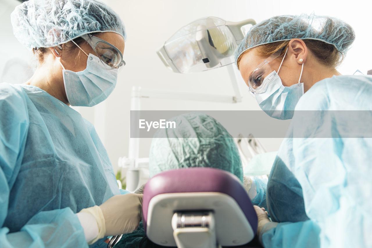 Dentists examining woman at clinic