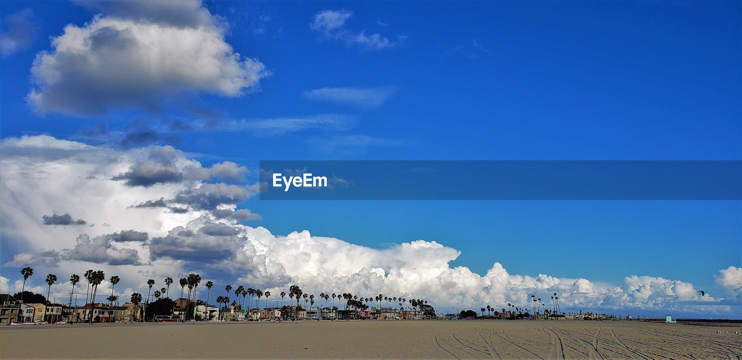 PANORAMIC SHOT OF PEOPLE ON BEACH AGAINST BLUE SKY