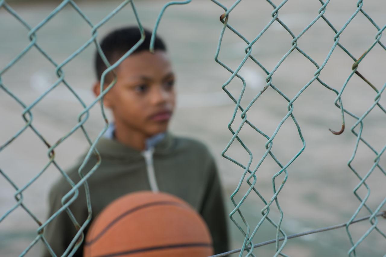 Boy Holding Ball Seen Through Broken Chainlink Fence