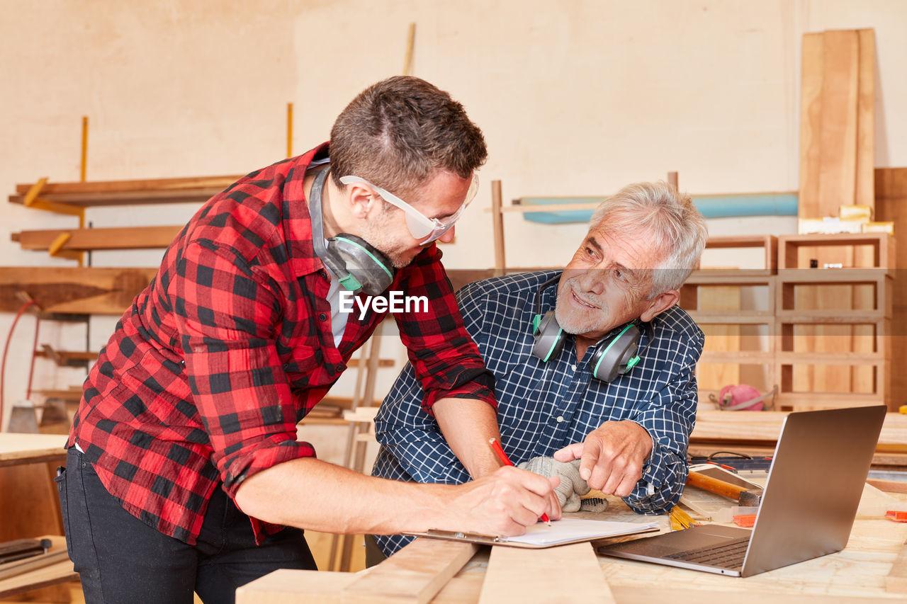 Smiling carpenters having discussion at workshop