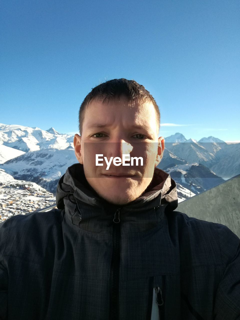 Portrait Of Young Man Against Snowcapped Mountains
