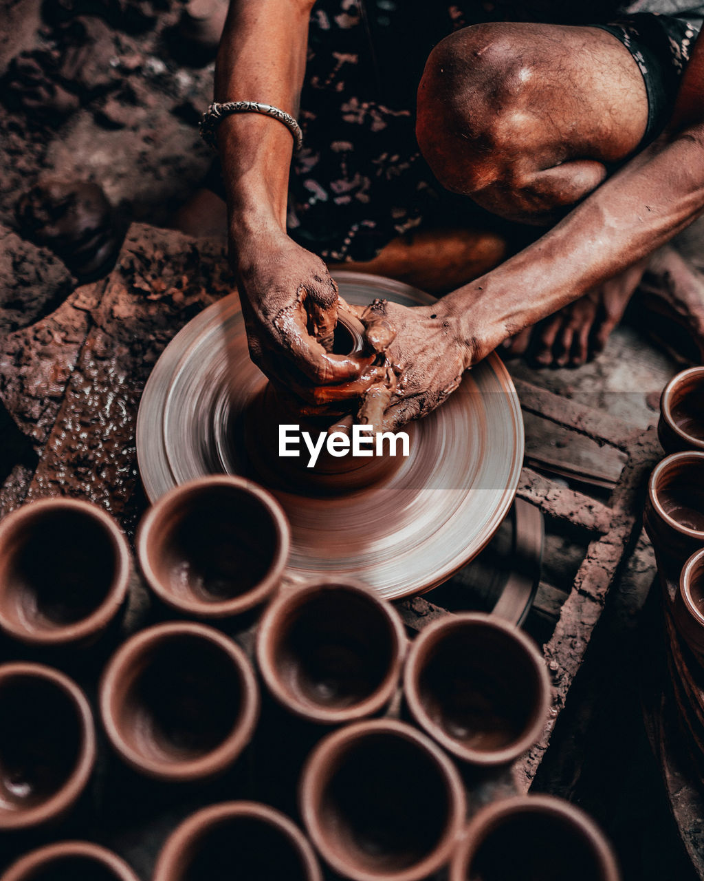 occupation, one person, human hand, men, hand, real people, skill, working, pottery, making, human body part, preparation, clay, expertise, industry, art and craft, workshop, molding a shape, craft, outdoors, mud