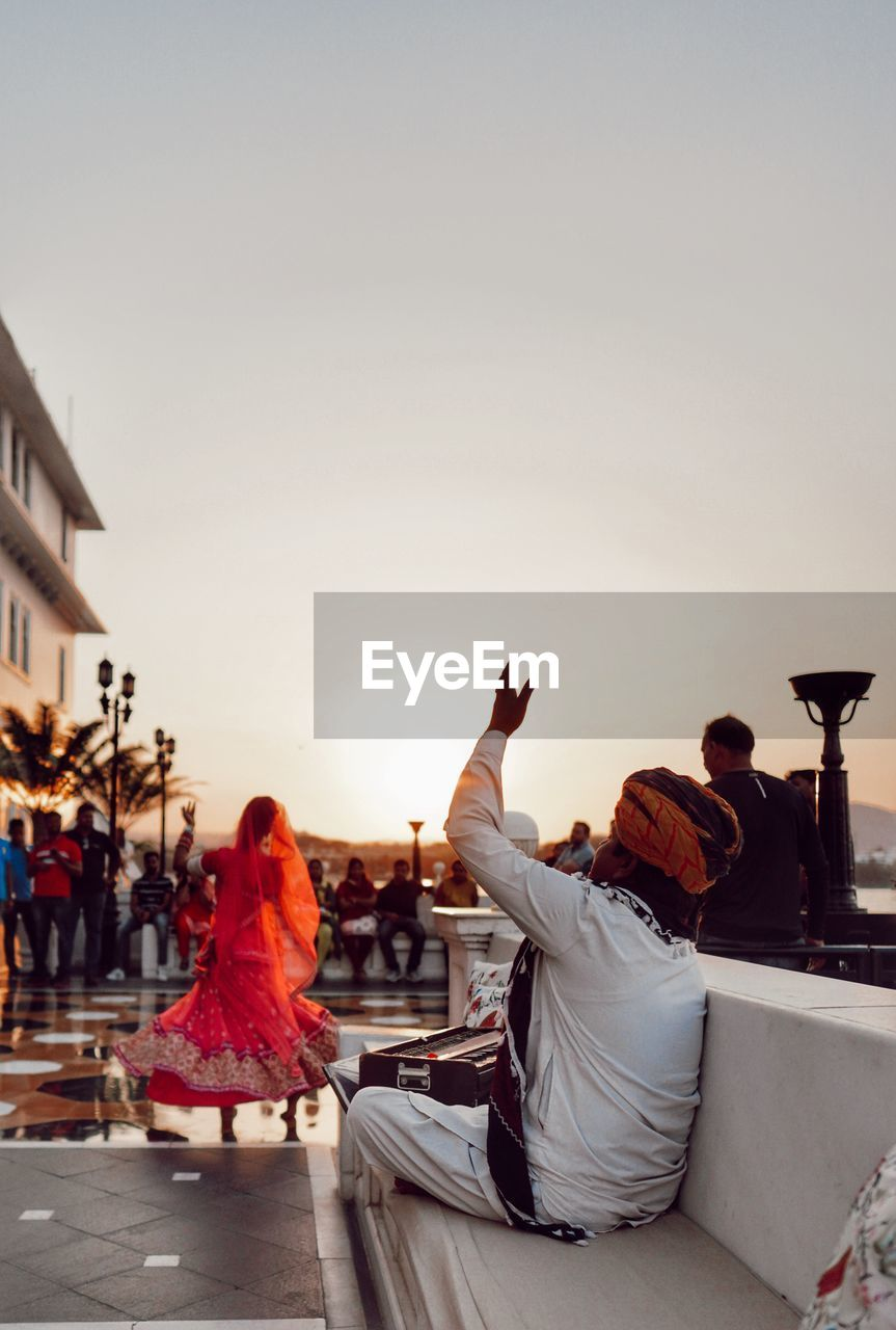 real people, sky, women, lifestyles, sitting, men, sunset, group of people, adult, people, leisure activity, rear view, clear sky, copy space, incidental people, nature, architecture, building exterior, togetherness, traditional clothing, outdoors