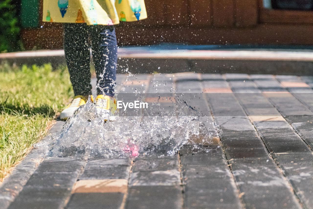Low Section Of Girl Splashing Water Bomb