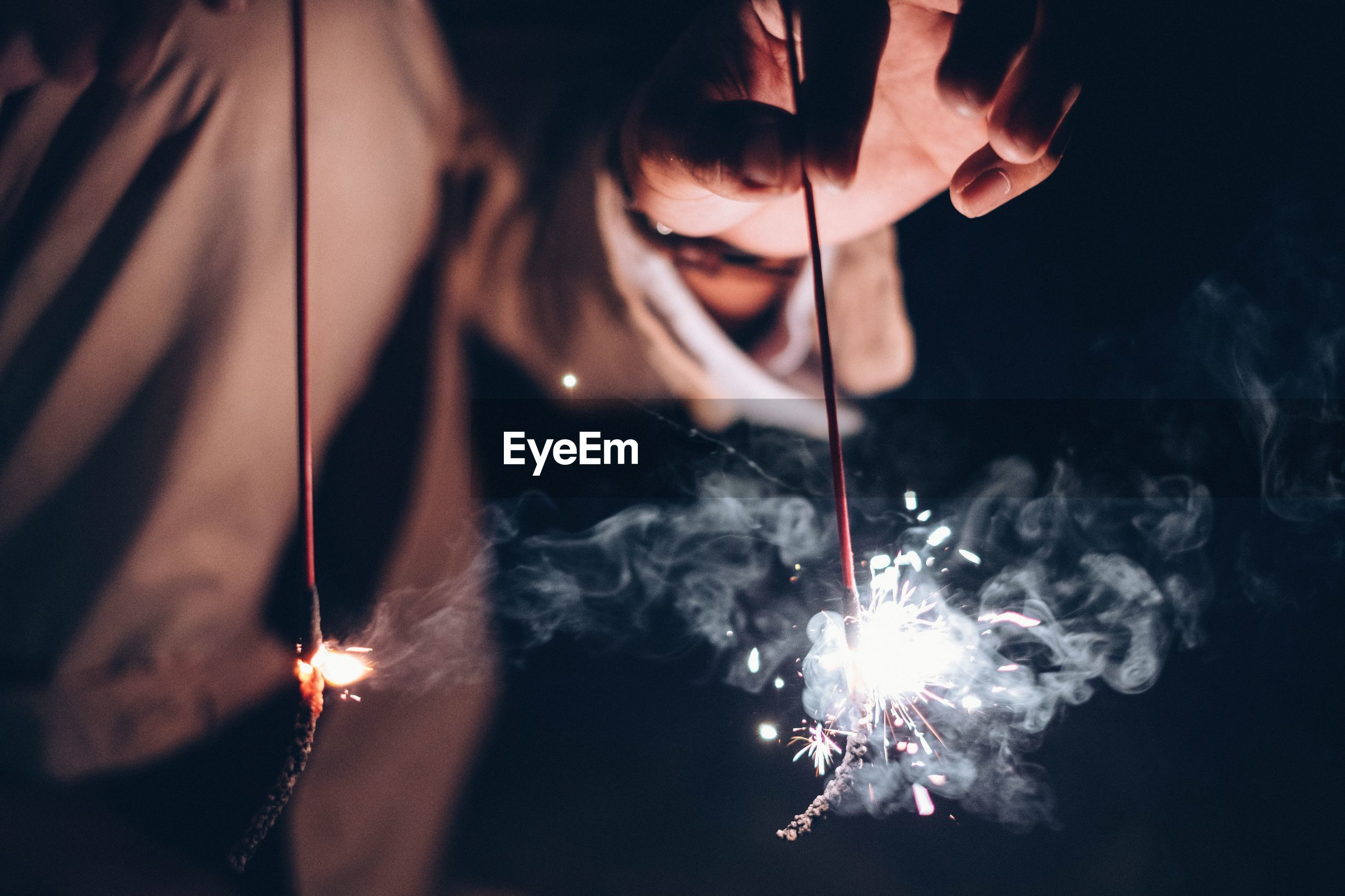 Midsection of woman holding lit sparklers at night