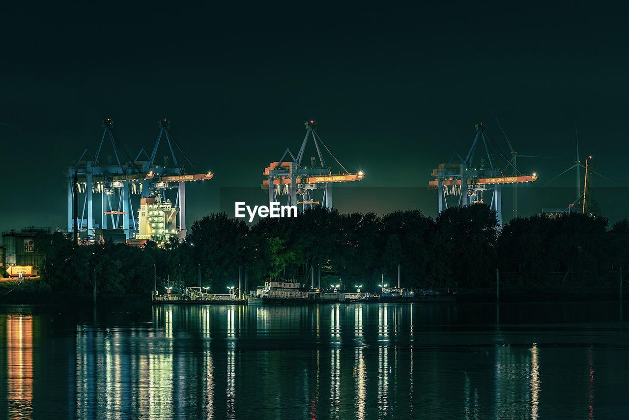 Cranes By Lake At Night