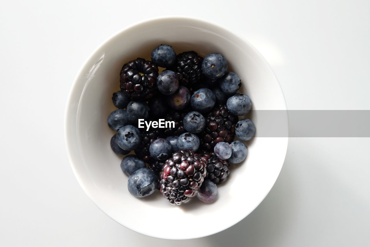 Directly above shot of berries in bowl on white background