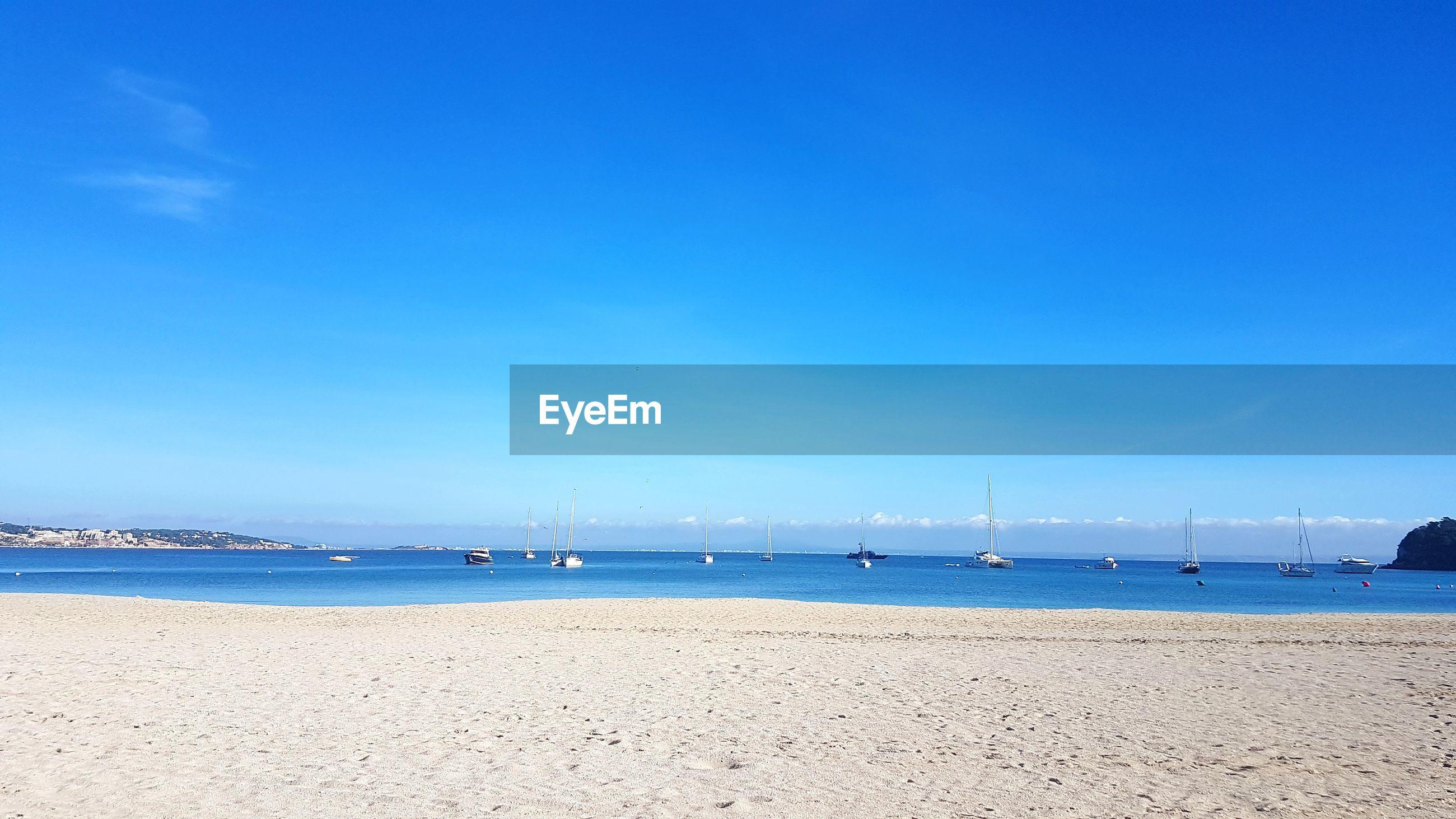 SAILBOATS ON SEA AGAINST BLUE SKY