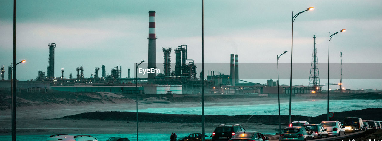 transportation, sky, mode of transportation, industry, water, no people, nature, motor vehicle, smoke stack, sea, car, architecture, building exterior, built structure, nautical vessel, outdoors, panoramic, lighting equipment, land vehicle, pollution