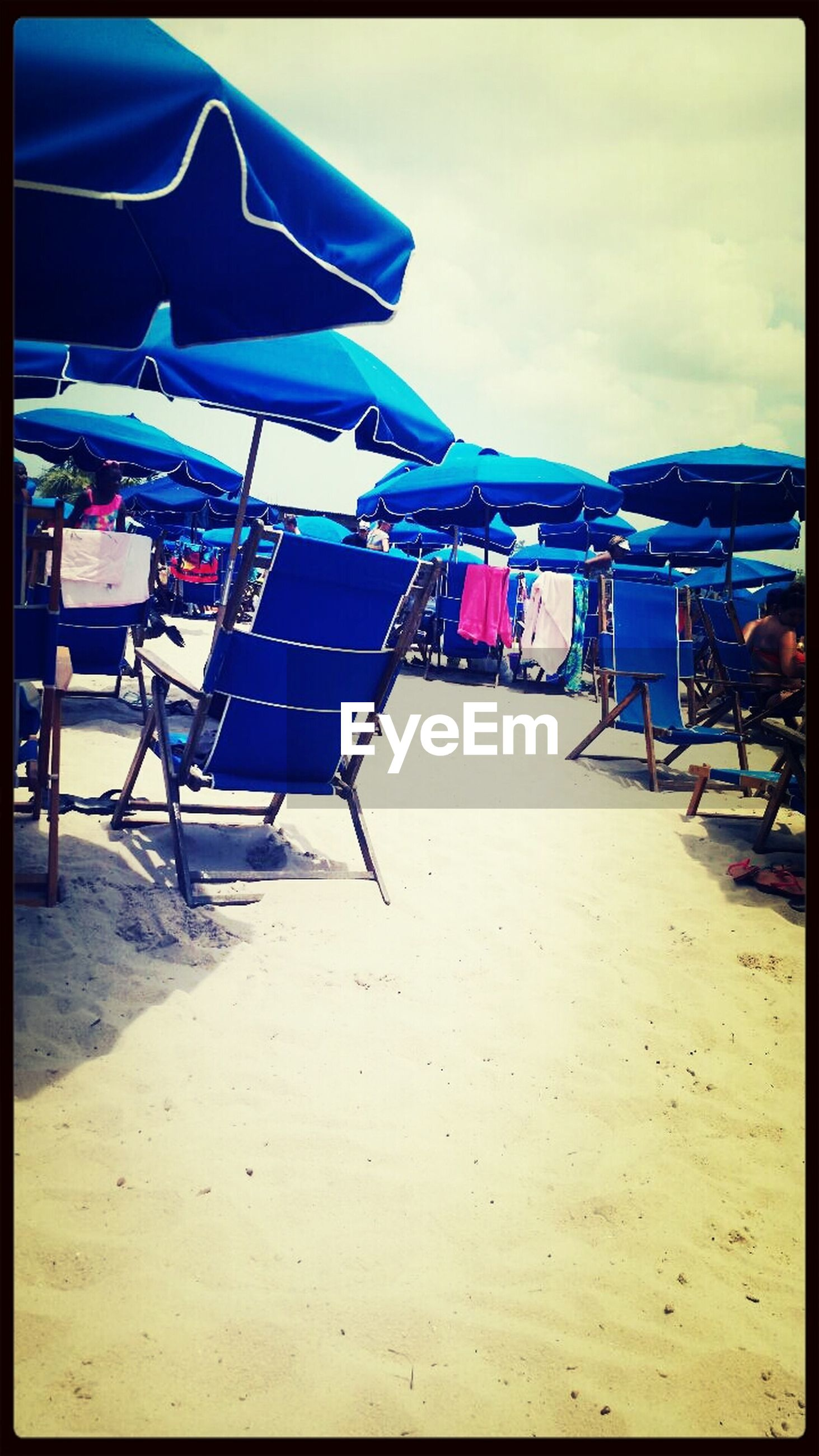 beach, sand, sky, sea, beach umbrella, shore, auto post production filter, absence, parasol, transfer print, sunlight, built structure, moored, day, blue, lounge chair, chair, outdoors, incidental people, in a row