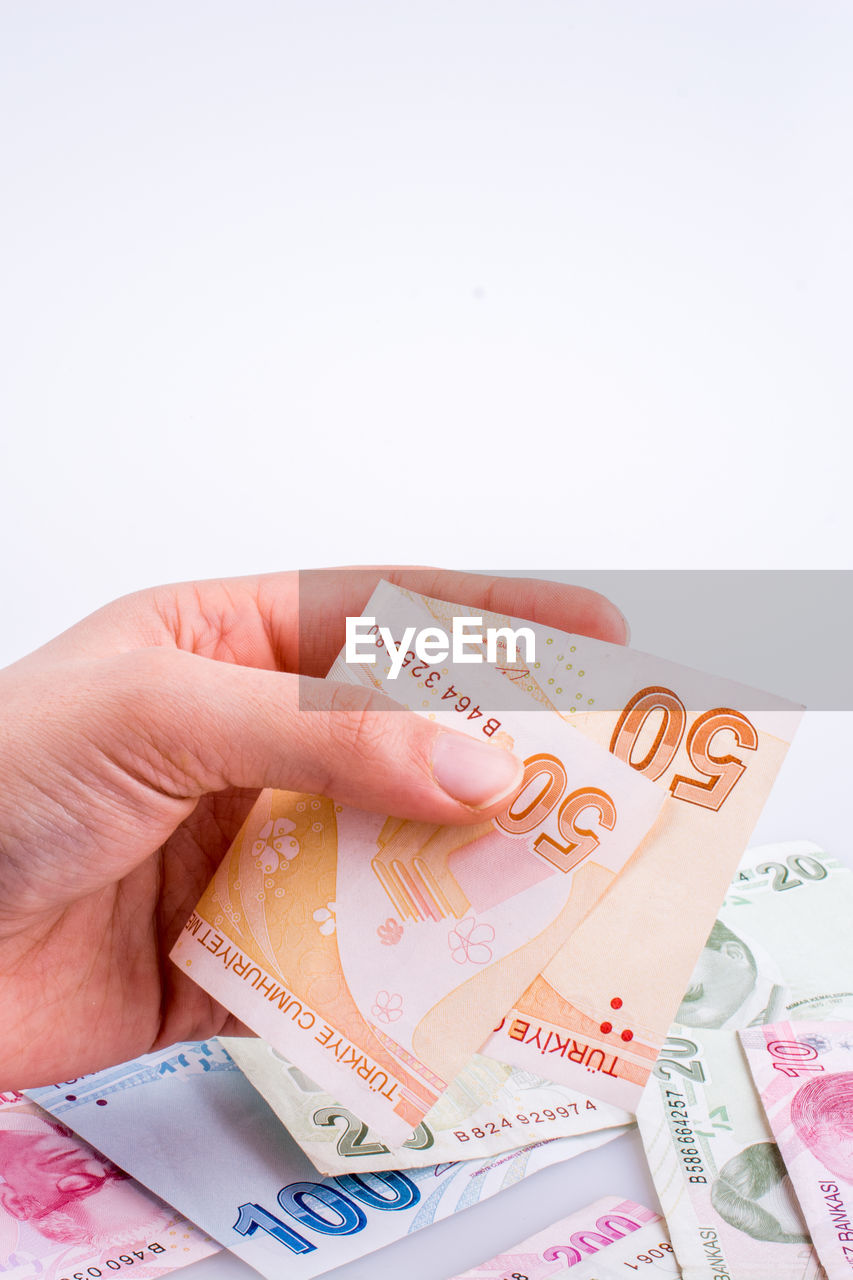 finance, human hand, hand, currency, human body part, business, paper currency, wealth, copy space, one person, indoors, holding, white background, unrecognizable person, studio shot, body part, investment, close-up, economy, finger, financial item