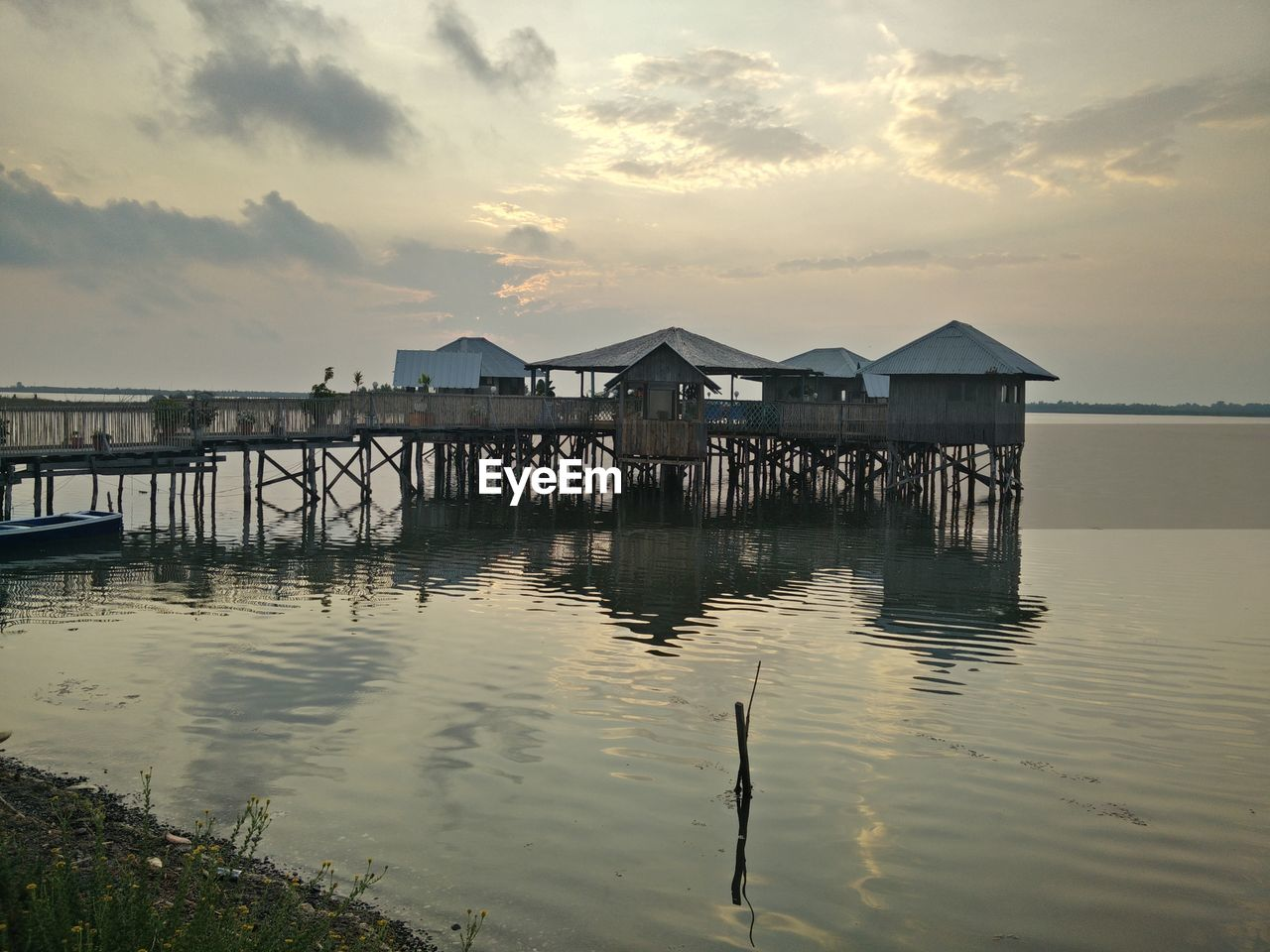 sky, water, built structure, architecture, sunset, stilt, outdoors, tranquil scene, tranquility, stilt house, sea, nature, cloud - sky, no people, beauty in nature, scenics, building exterior, day