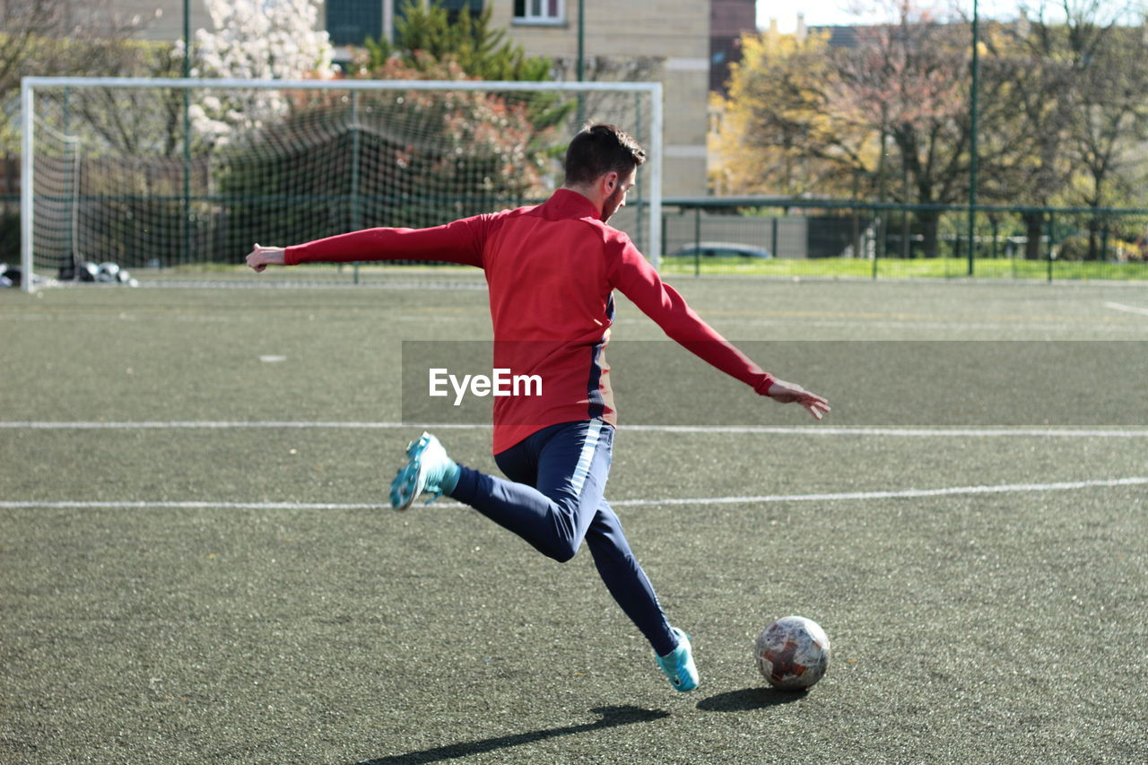 sport, soccer, team sport, playing, soccer ball, full length, ball, leisure activity, child, sports equipment, motion, sports clothing, soccer field, clothing, athlete, men, one person, boys, childhood, lifestyles, skill, outdoors, goalie
