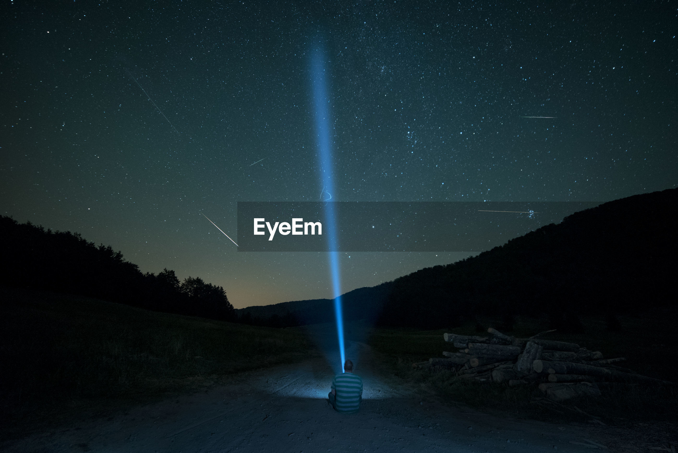 Rear view of man with illuminated flashlight sitting against star field at night