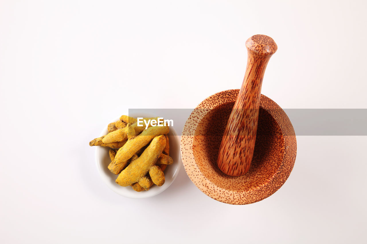 Close-up of turmeric with mortar and pestle over white background