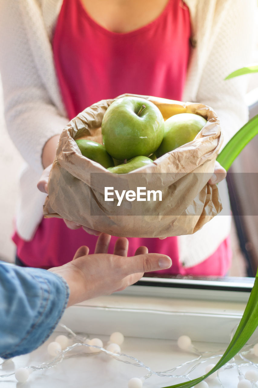 Close-Up Of People With Granny Smith Apple
