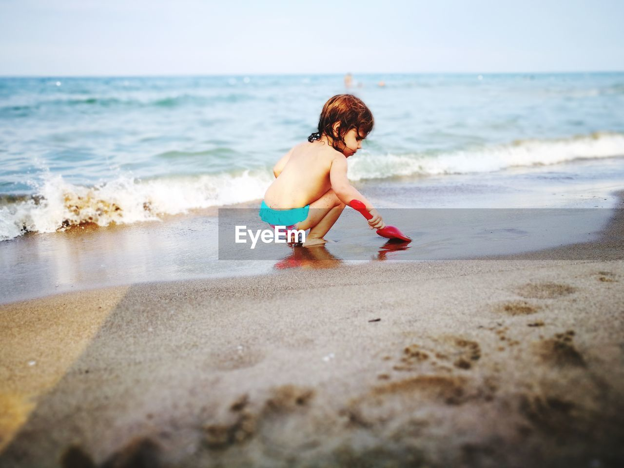 Full Length Of Shirtless Baby Girl Playing On Shore At Beach