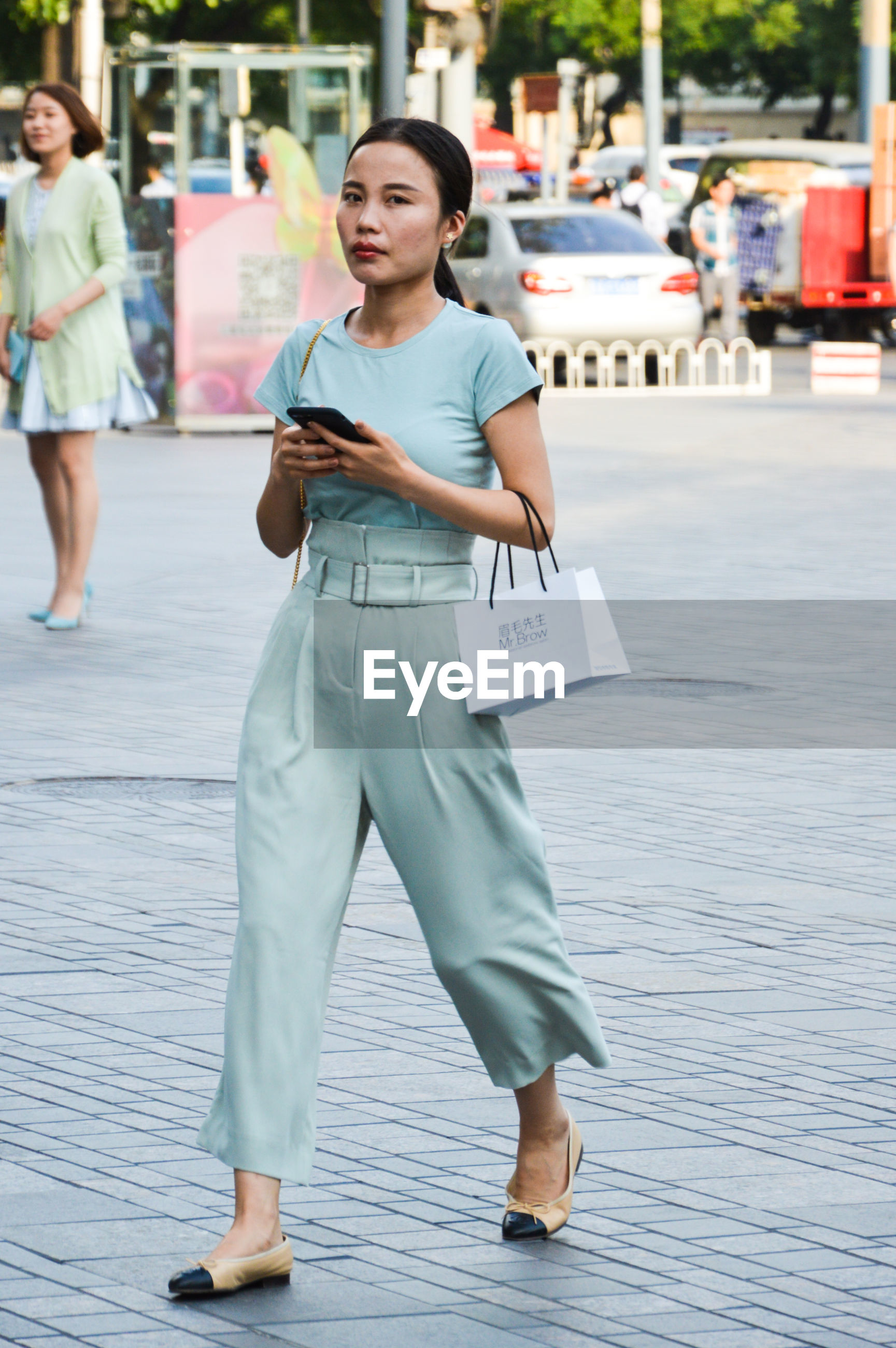 full length, leisure activity, casual clothing, young adult, communication, real people, front view, young women, one person, wireless technology, lifestyles, holding, walking, day, outdoors, focus on foreground, mobile phone, beautiful woman