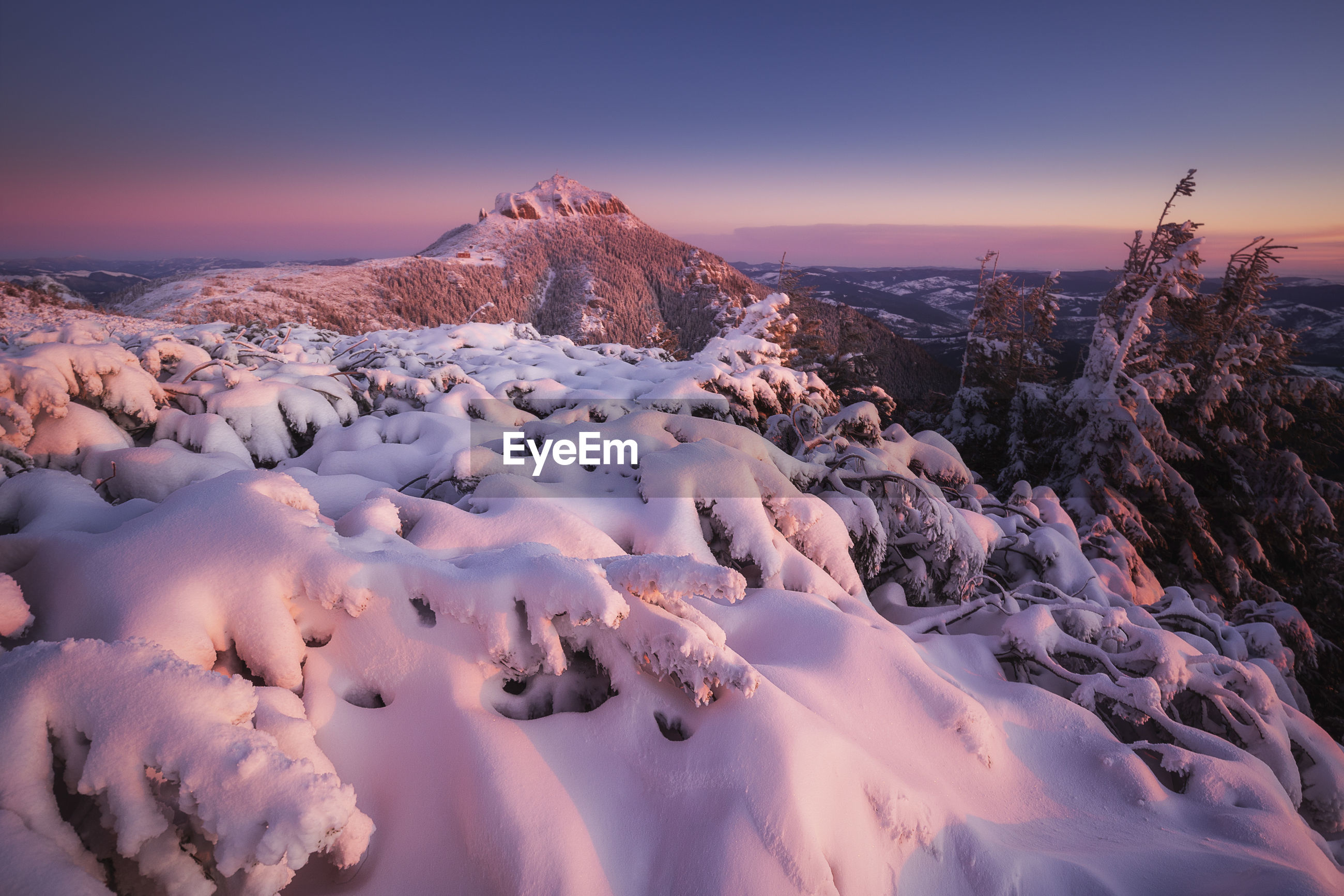 Snow covered landscape against sky during sunset in ceahlau mountains