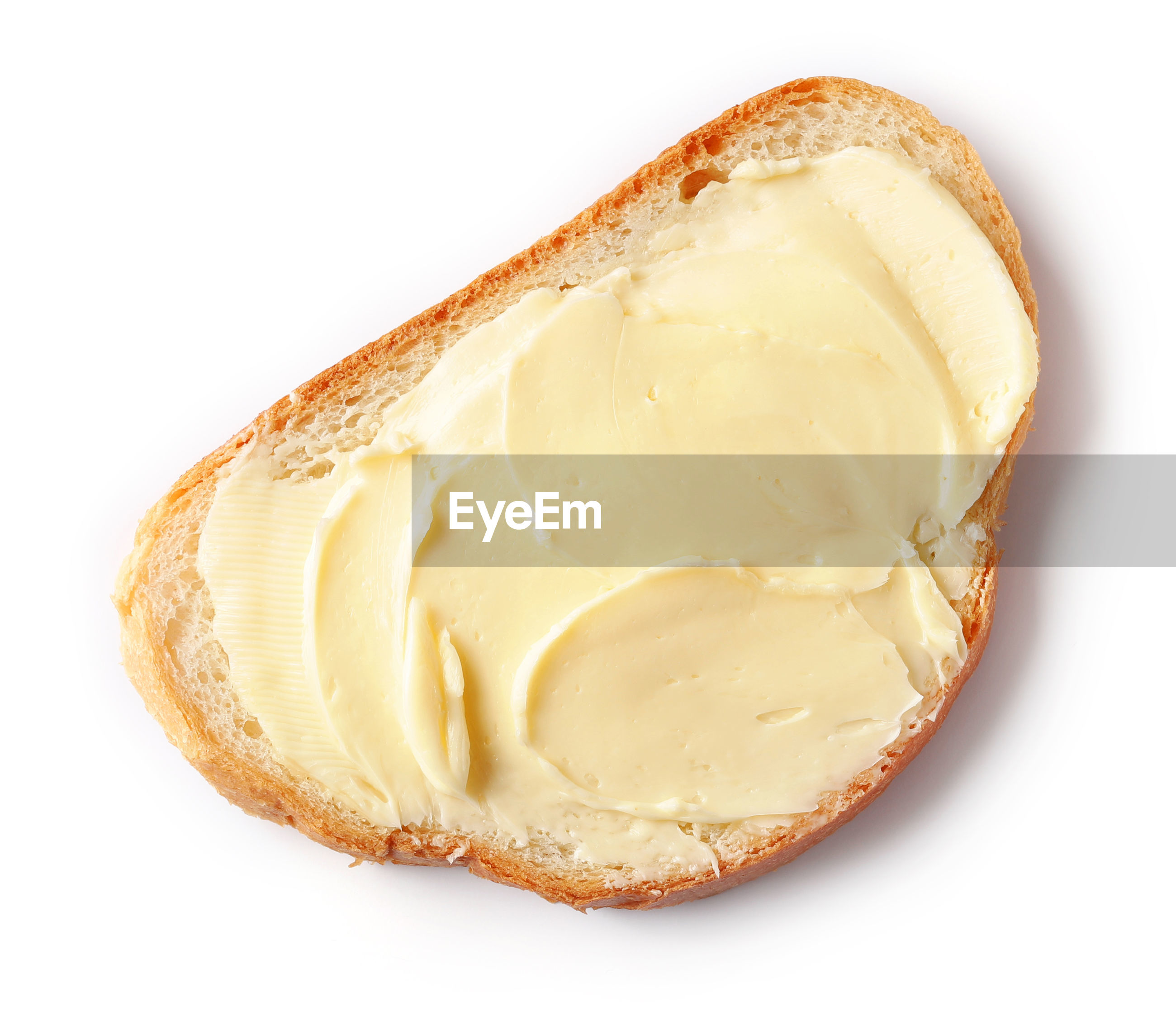Close-up of margarine spread on bread against white background