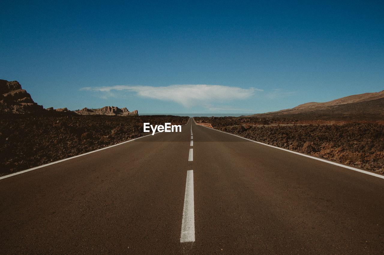 Empty road along landscape and blue sky