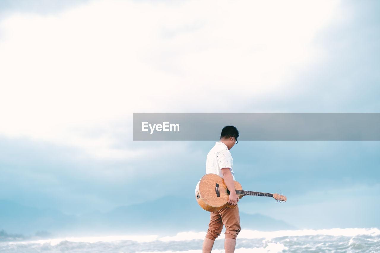 Man Holding Guitar Walking At Sea Shore Against Sky