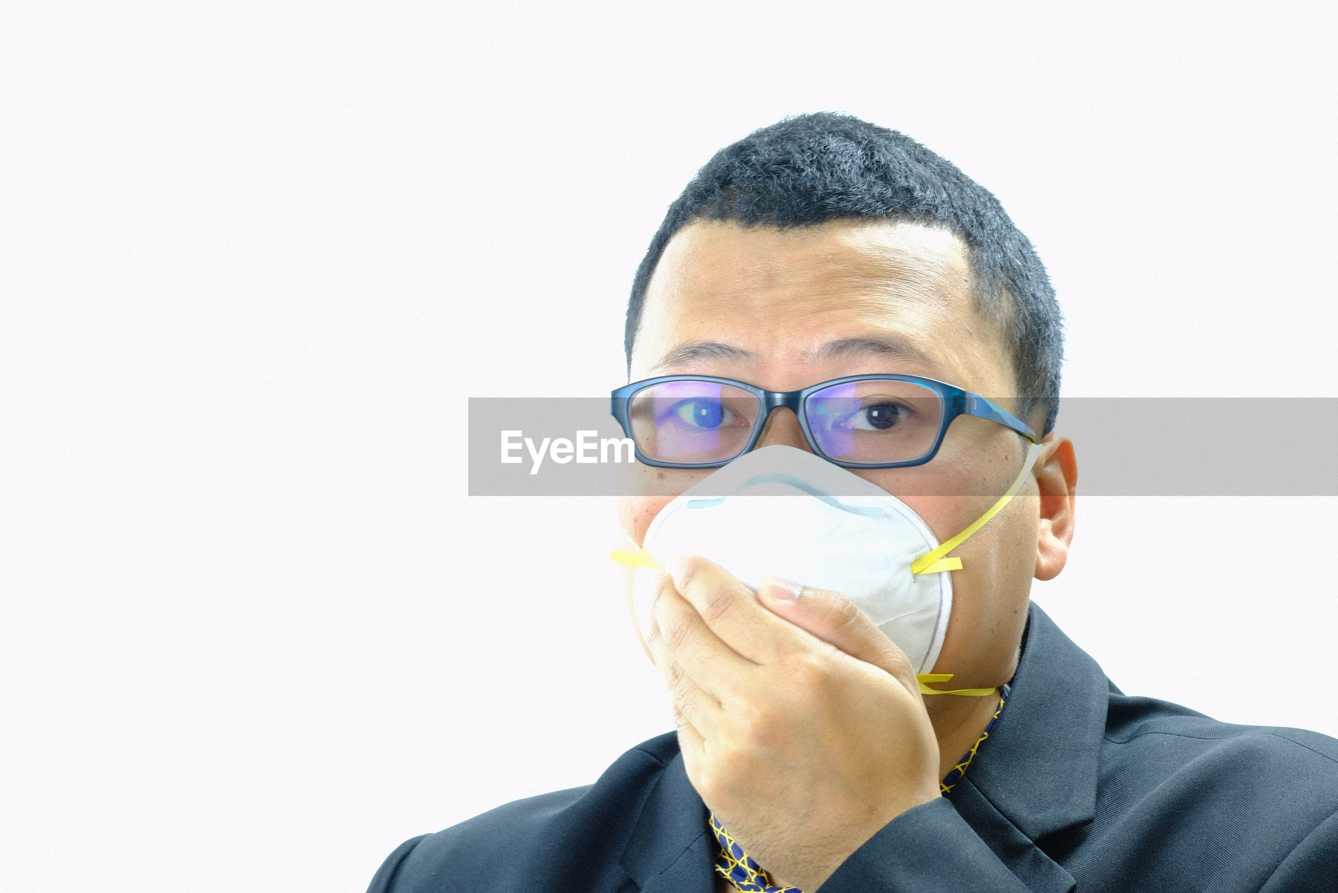 Portrait of businessman wearing pollution mask against white background