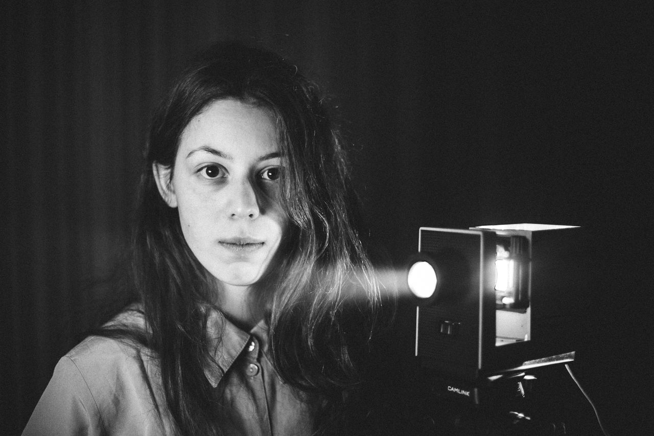 Close-Up Portrait Of Young Woman By Video Camera