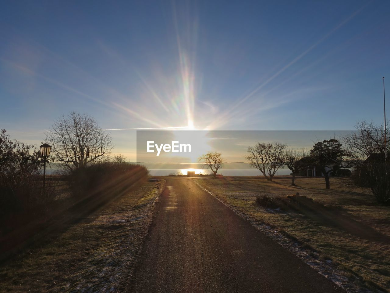 sun, sunlight, sunset, sky, sunbeam, tree, lens flare, bare tree, outdoors, beauty in nature, nature, tranquil scene, tranquility, scenics, field, no people, rural scene, grass, day, vapor trail