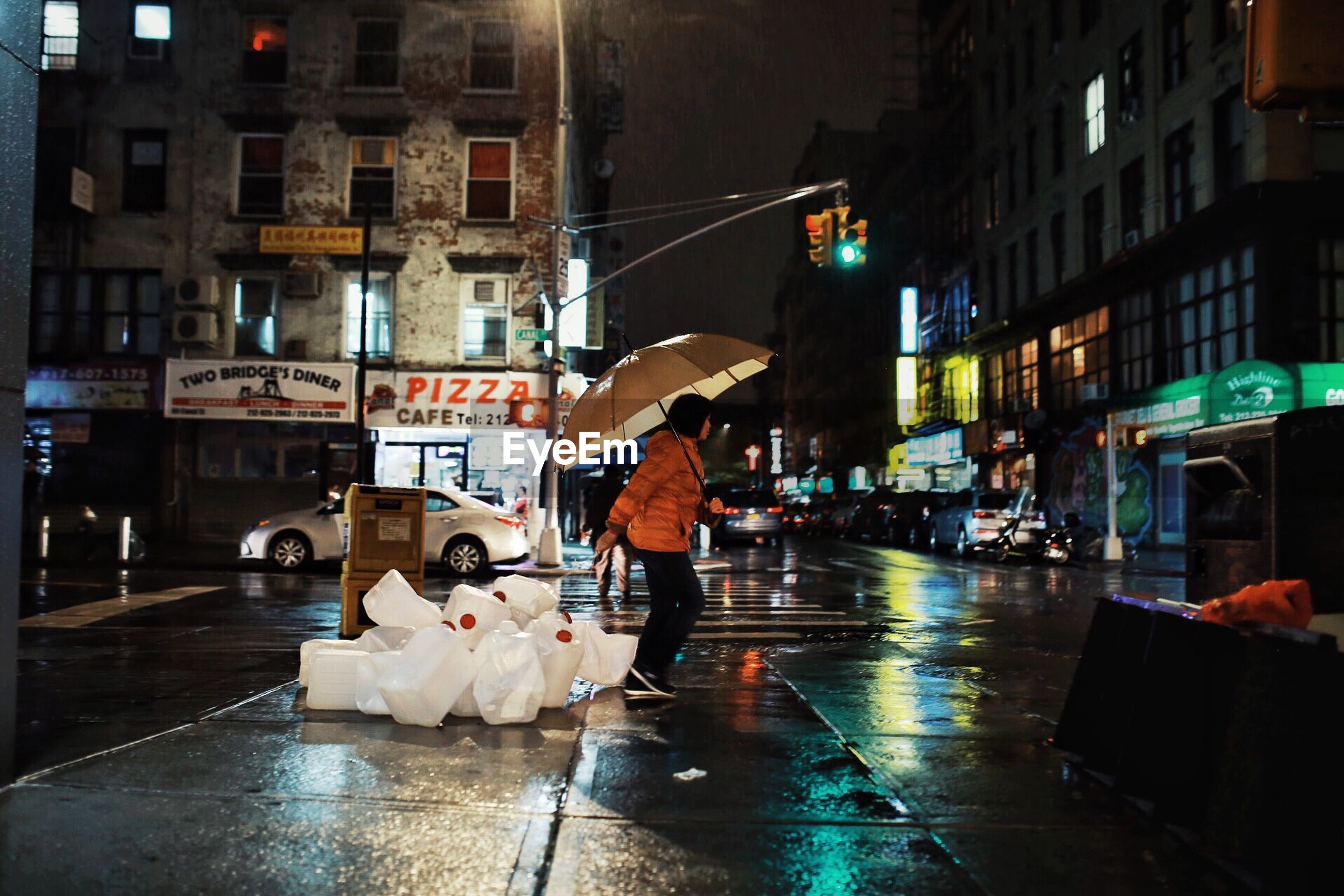 city, building exterior, street, architecture, wet, umbrella, rain, built structure, real people, city life, protection, walking, men, transportation, people, city street, illuminated, motor vehicle, lifestyles, rainy season