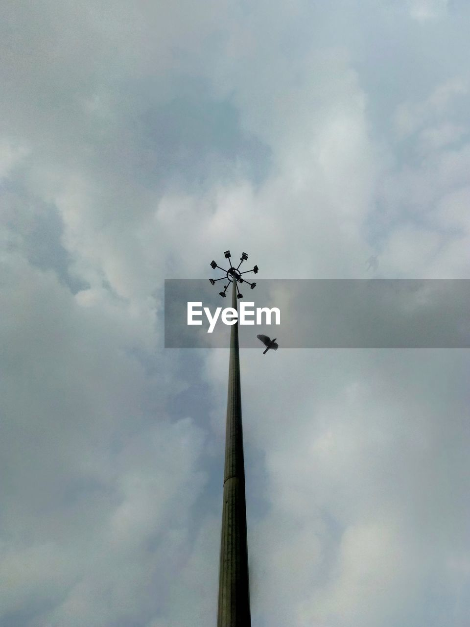 low angle view, cloud - sky, sky, no people, nature, day, outdoors, floodlight, mode of transportation, airplane, tall - high, flying, transportation, built structure, air vehicle, religion, overcast, architecture, lighting equipment, pole, directly below, plane