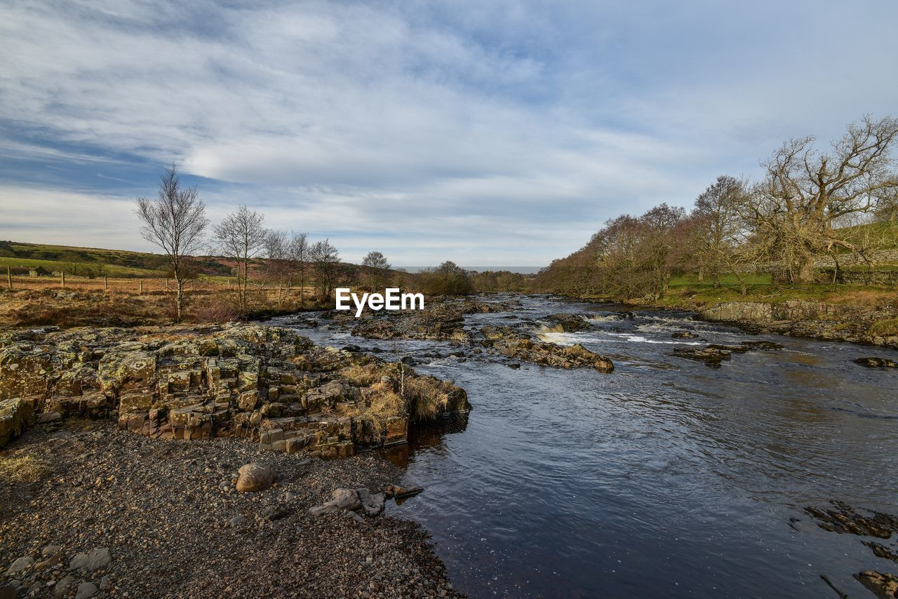 water, sky, beauty in nature, rock, cloud - sky, tranquility, nature, scenics - nature, tree, tranquil scene, river, solid, rock - object, no people, plant, day, non-urban scene, land, outdoors, flowing water, flowing, stream - flowing water, shallow