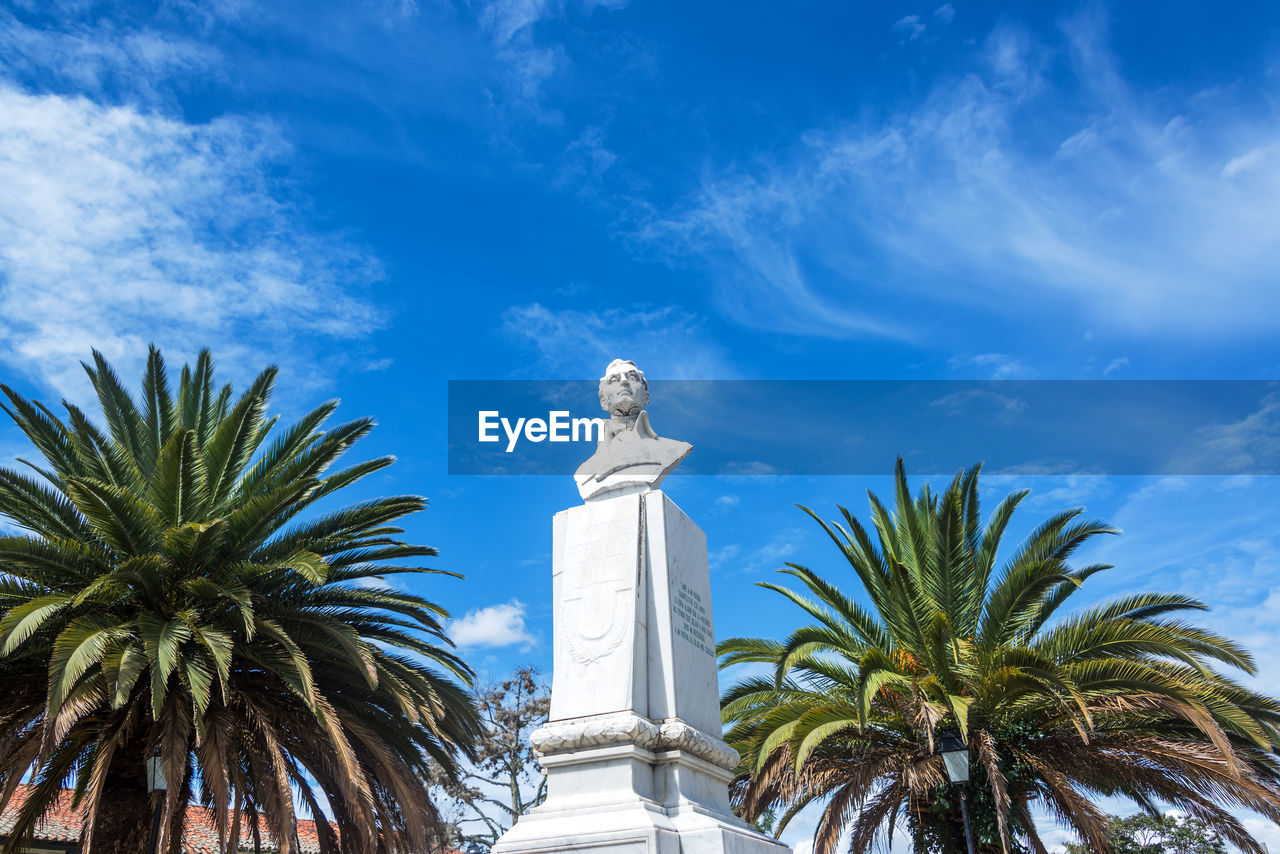 statue, sculpture, sky, human representation, palm tree, low angle view, tree, no people, day, architecture, outdoors