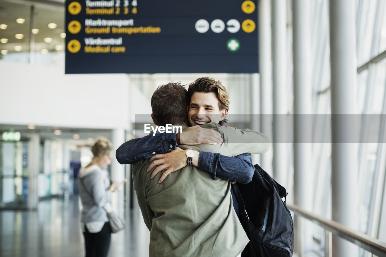 togetherness, women, focus on foreground, adult, two people, emotion, indoors, real people, airport, men, people, love, standing, casual clothing, positive emotion, smiling, transportation, embracing, happiness, couple - relationship