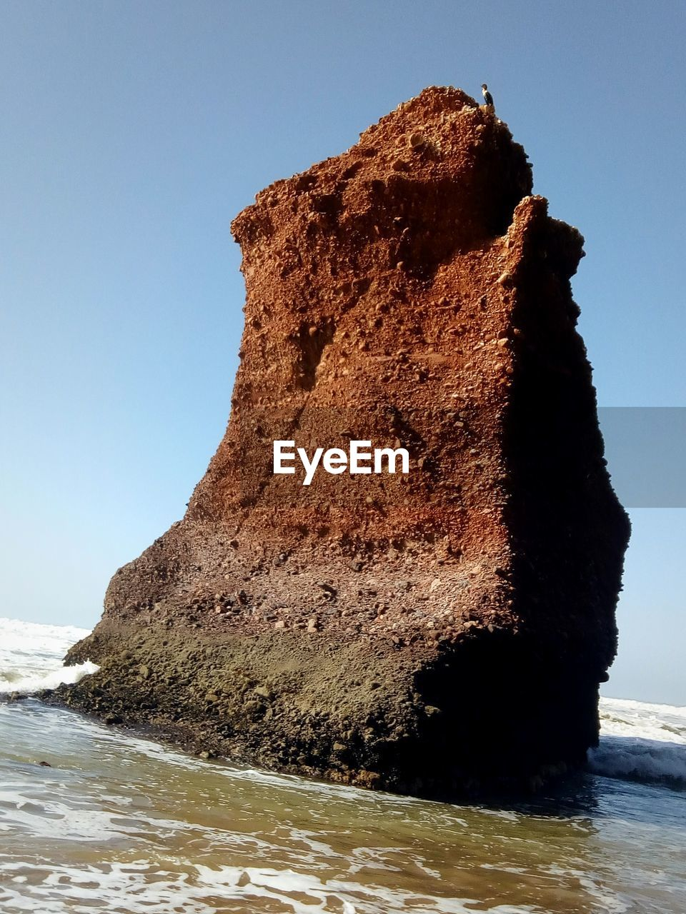 ROCK FORMATION ON SHORE AGAINST CLEAR SKY