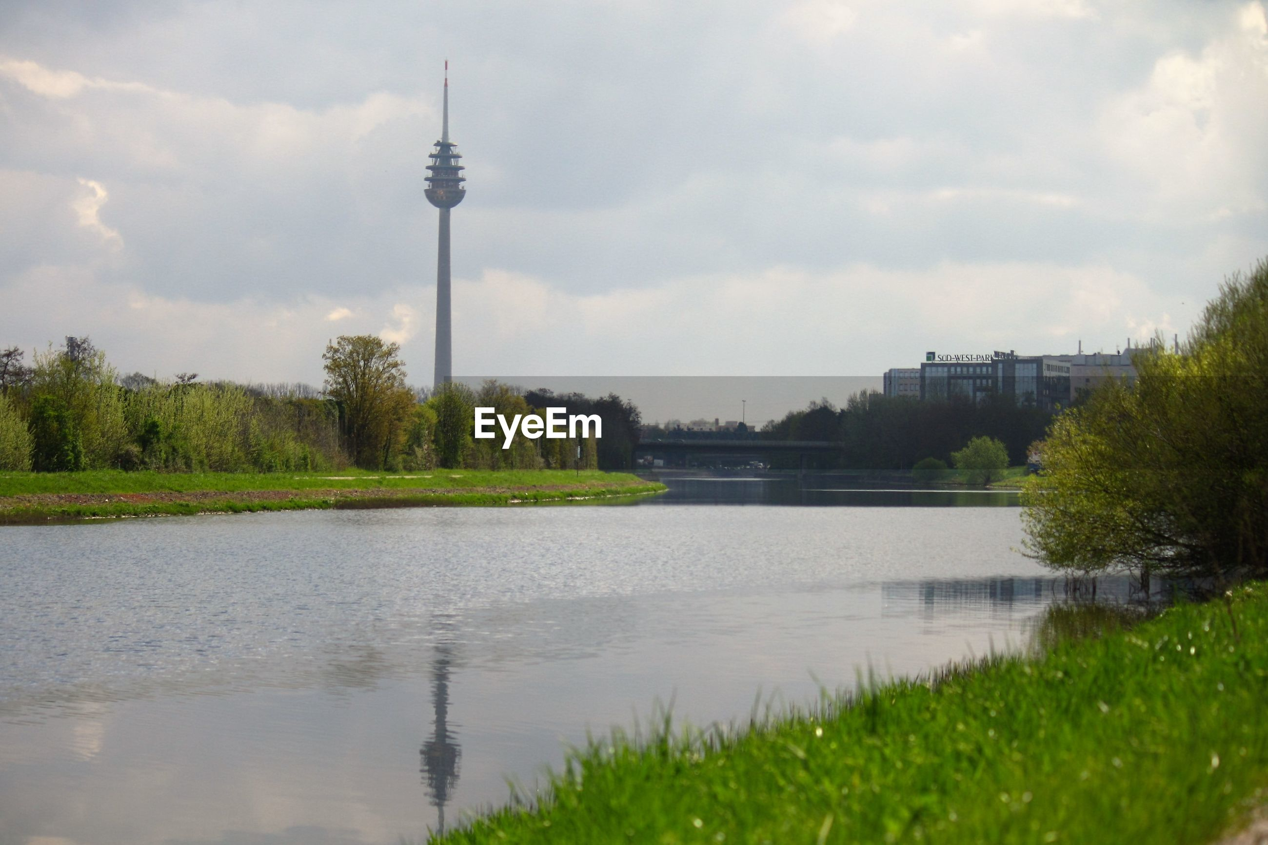 Communication tower by river against sky in city