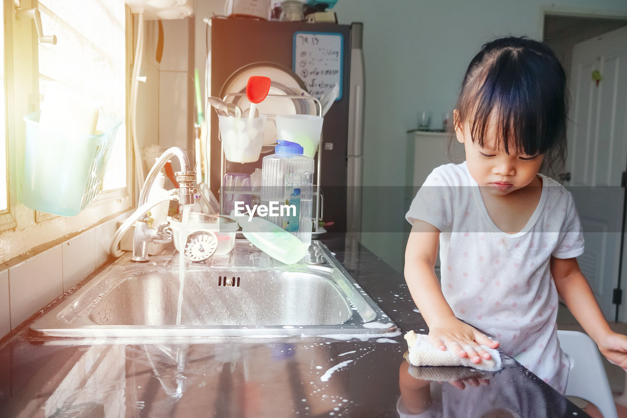 Cute girl cleaning table in kitchen
