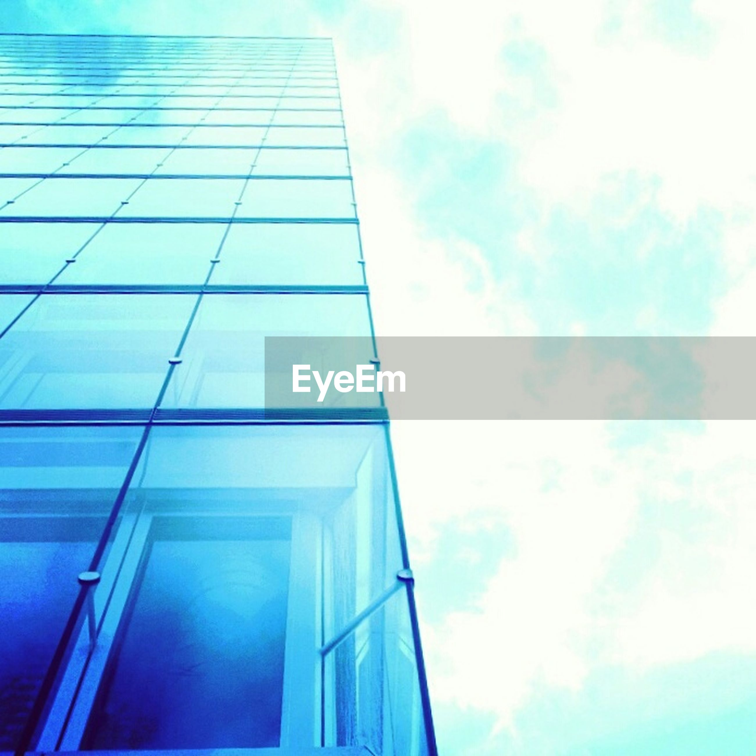 low angle view, architecture, building exterior, built structure, modern, sky, office building, tall - high, glass - material, cloud - sky, building, blue, reflection, city, skyscraper, cloud, tower, window, day, outdoors