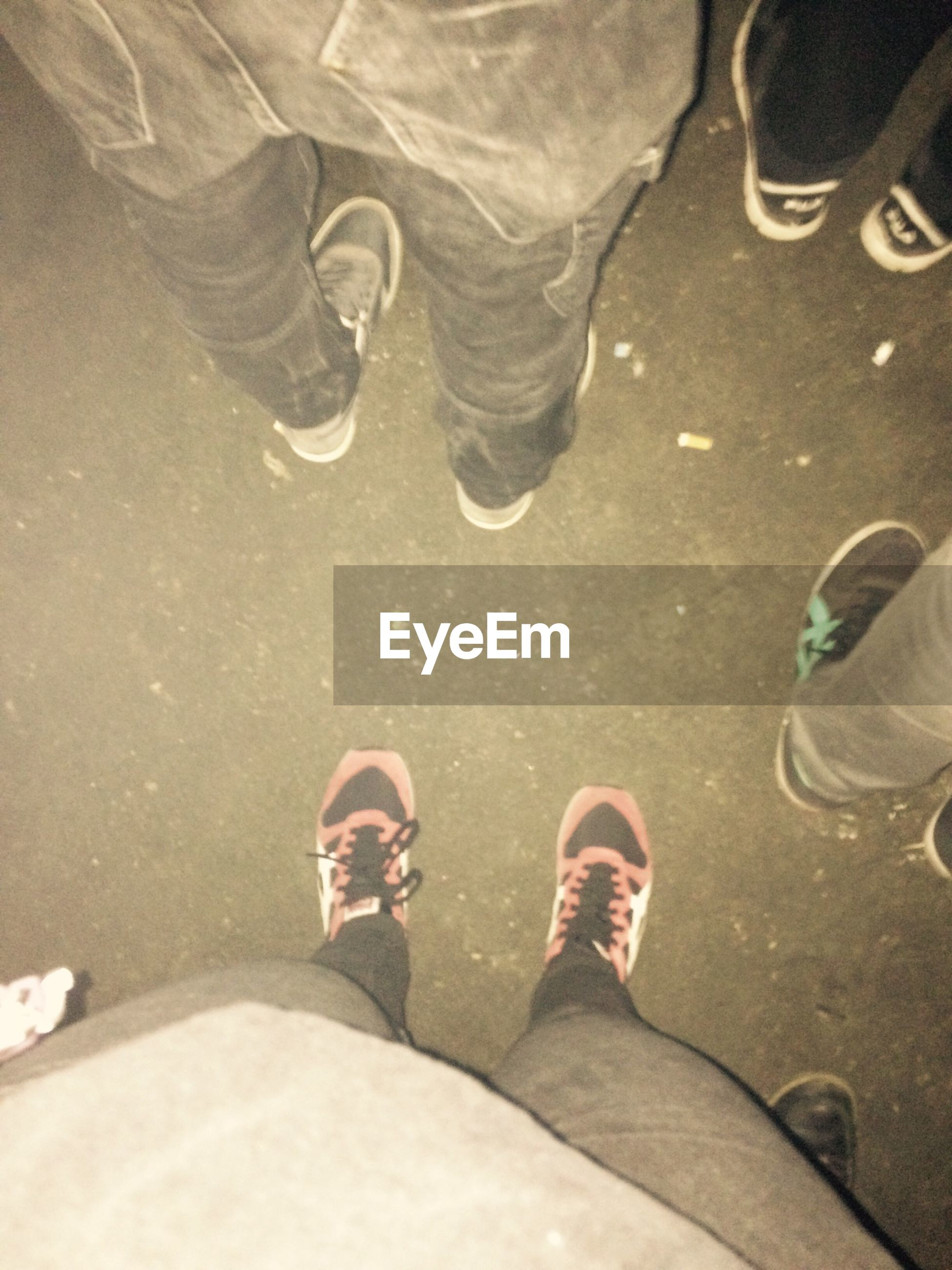 low section, person, shoe, personal perspective, footwear, human foot, standing, lifestyles, high angle view, men, jeans, leisure activity, street, casual clothing, canvas shoe, unrecognizable person