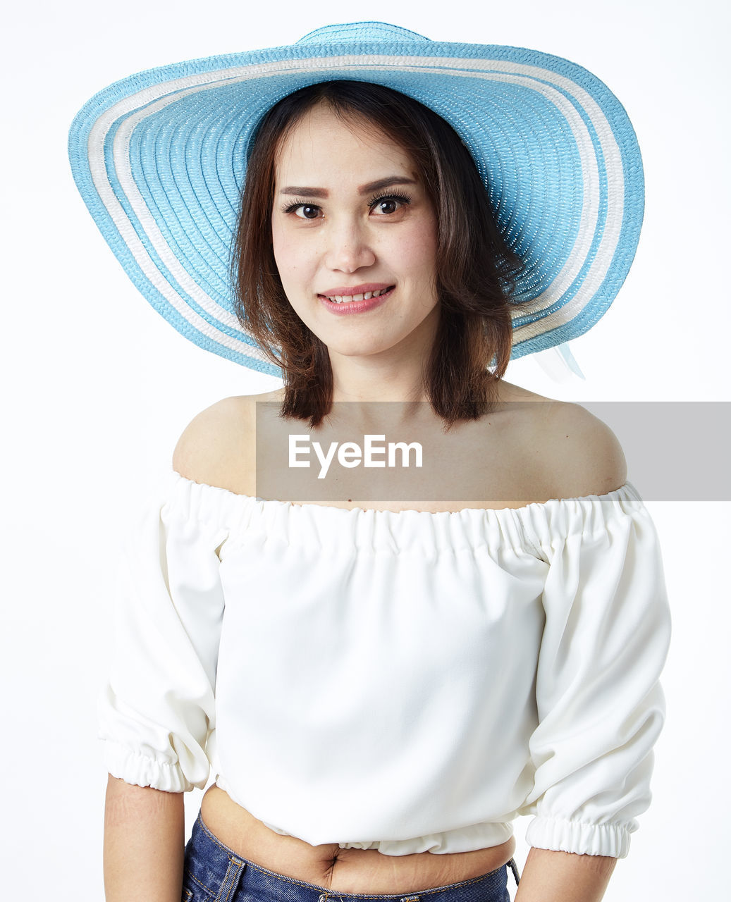 front view, looking at camera, portrait, one person, young adult, young women, hat, casual clothing, indoors, smiling, clothing, standing, leisure activity, women, studio shot, lifestyles, three quarter length, white background, hair, hairstyle, beautiful woman