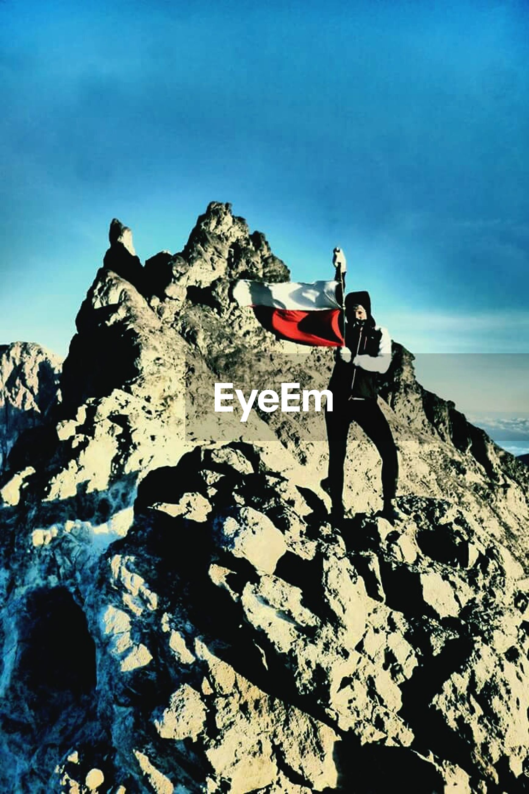 transportation, rock - object, leisure activity, lifestyles, adventure, sky, men, mode of transport, rock formation, sunlight, extreme sports, full length, mountain, blue, travel, low angle view, land vehicle, day