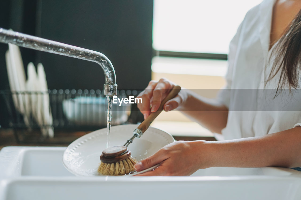 Midsection of woman midsection of woman cleaning dishes at home