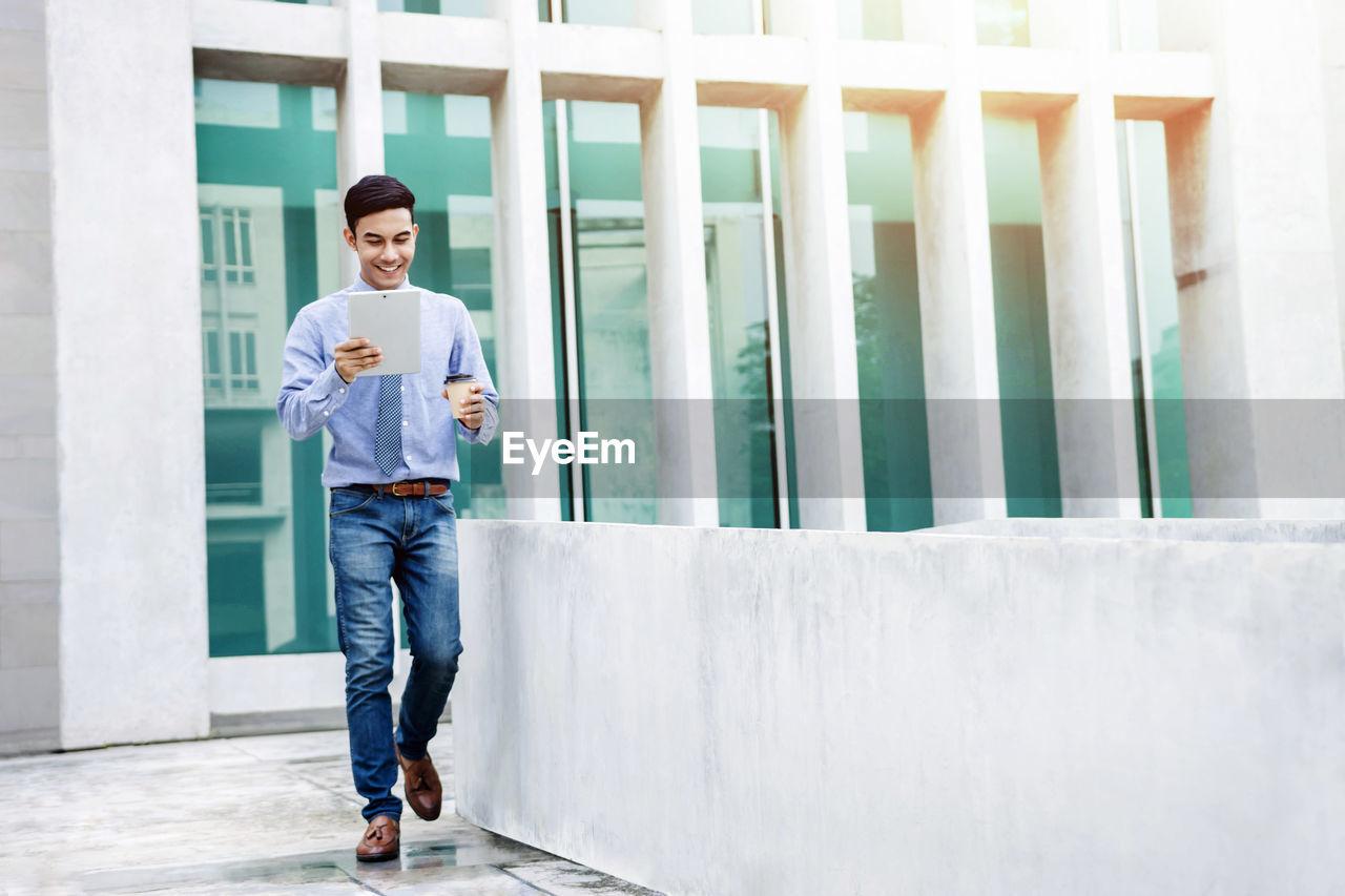 Businessman Using Digital Tablet While Walking Against Building