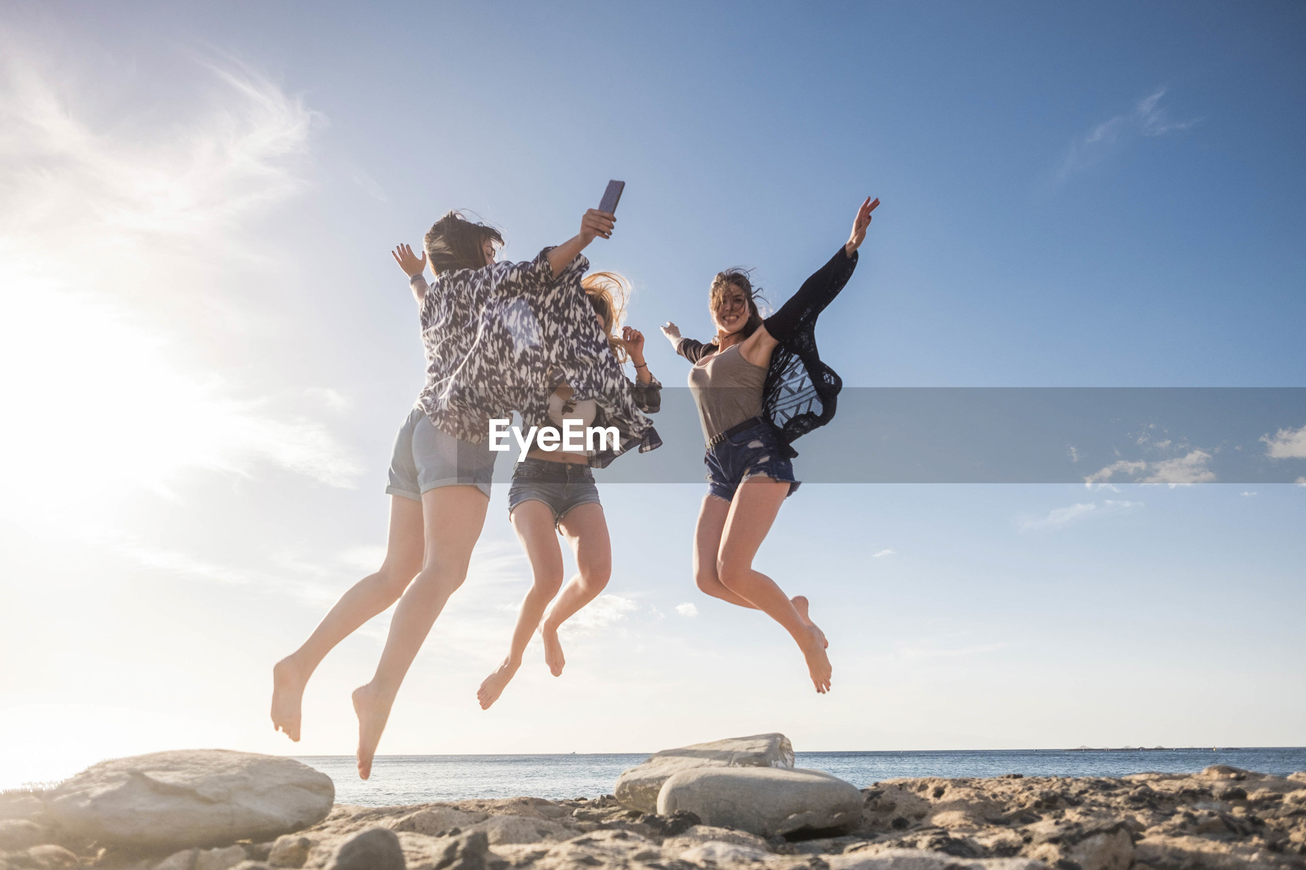 Friends jumping at beach against sky