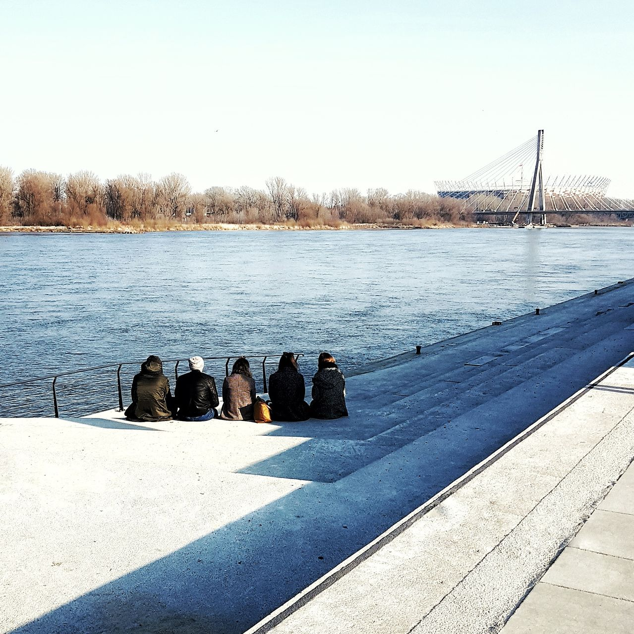 REAR VIEW OF PEOPLE SITTING BY LAKE AGAINST SKY